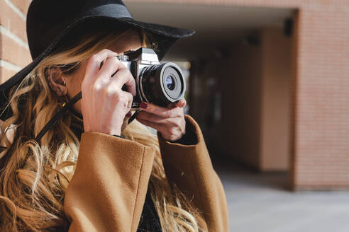 Young woman in hat filming through camera during sunny day - FMOF01359