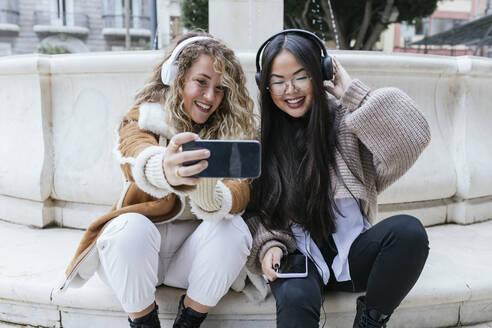 Smiling female friends taking selfie wearing headphones while sitting against fountain - JRVF00208
