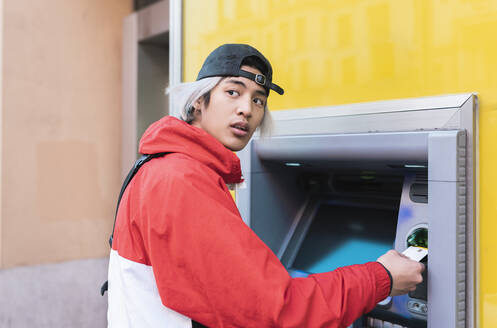 Young man withdrawing money at ATM machine - JCCMF01126