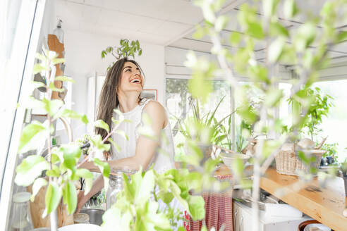 Laughing woman looking up while doing plantation in house - GGGF00938