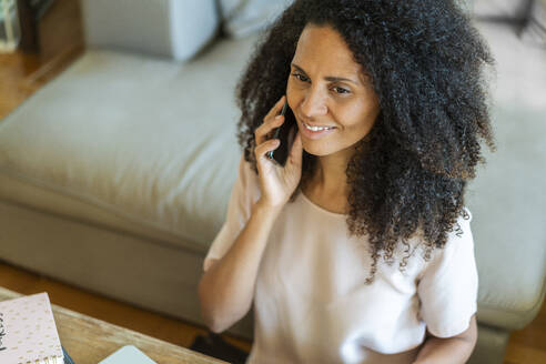 Mid adult businesswoman talking on smart phone while sitting at home - AKLF00020