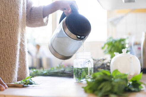 Woman's hand pouring water in jar to prepare tea in kitchen - AKLF00029
