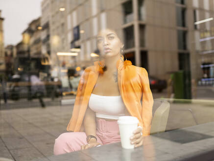 Young woman contemplating with coffee cup in cafe - JCCMF01162