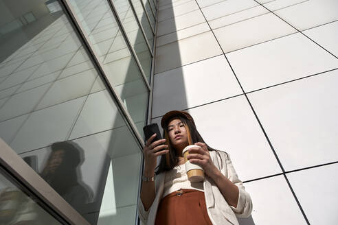 Beautiful woman with reusable cup using smart phone while standing against wall - VEGF03798