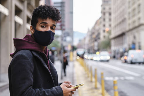 Young man wearing protective face mask using mobile phone while standing in city - AGOF00001
