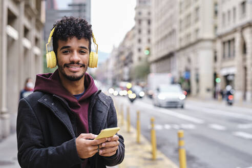 Smiling man with headphones using smart phone while standing on street in city - AGOF00004