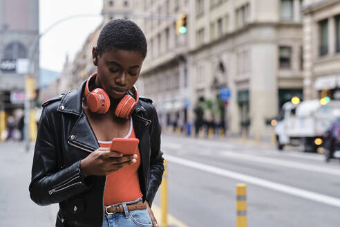Young woman with headphones using smart phone while standing in city - AGOF00007