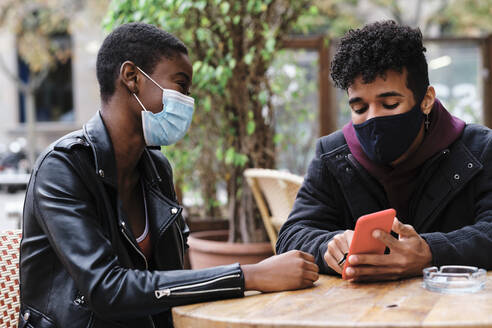 Friends wearing protective face mask using mobile phone while sitting at sidewalk cafe - AGOF00013