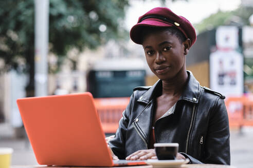 Young woman wearing jacket and cap using laptop while sitting at sidewalk cafe in city - AGOF00019