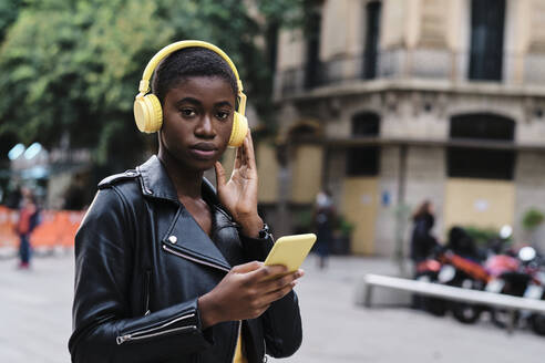 Woman listening music while standing in city - AGOF00025