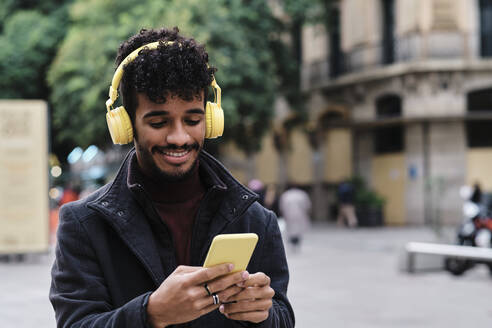 Smiling man wearing headphones using mobile phone while standing in city - AGOF00028