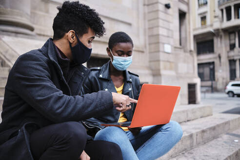 Man wearing protective face mask pointing at laptop while sitting with friend on steps - AGOF00034