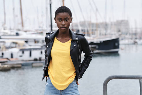 Young woman wearing jacket staring while standing with hands in pockets at harbor - AGOF00037