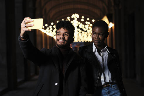Smiling man taking selfie through mobile phone while standing with friend at corridor - AGOF00043