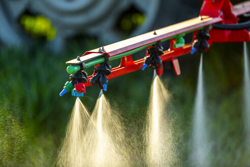 Close-up of tractor with crop sprayer sprinkling fertilizer in farm - NOF00136