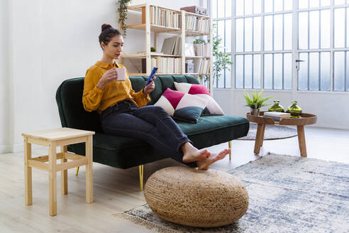 Woman with coffee cup using mobile phone while sitting on sofa at home - GIOF11021