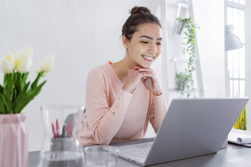 Young woman with hand on chin using laptop while talking with friend on laptop at home - GIOF11033