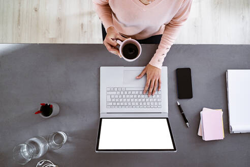 Young woman having coffee while using laptop while sitting at home - GIOF11048