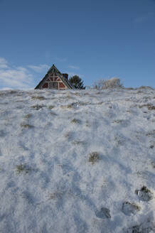 House roof peeking out from behind snow-covered levee - GISF00760