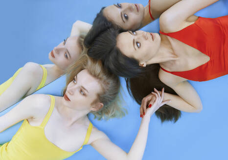 Female fashion models lying down on blue background while reflected in mirror - AZF00145