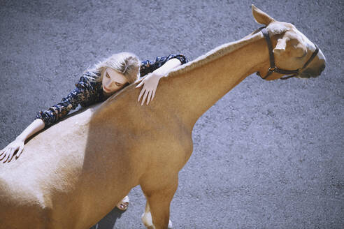 Young woman embracing horse on road - AZF00166