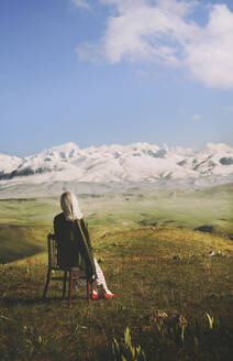Woman sitting on chair while looking at view against cloudy sky - AZF00169