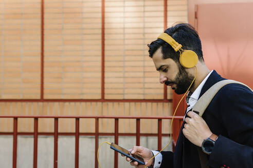 Businessman with headphones and backpack using mobile phone while standing by railing - XLGF01177