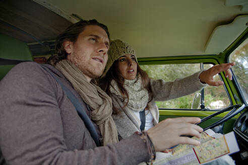 Woman guiding boyfriend while pointing out while sitting in camper van - AJOF01000