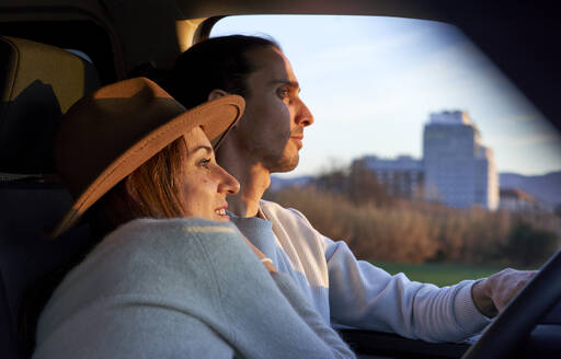 Man driving car while female embracing during sunset - VEGF03874