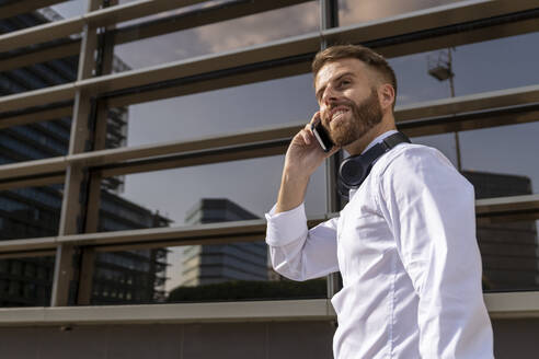 Smiling businessman talking on mobile phone while standing against building - BOYF01781