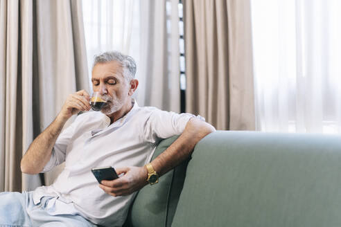 Mature man having coffee using smart phone while sitting on sofa in hotel room - DGOF01926