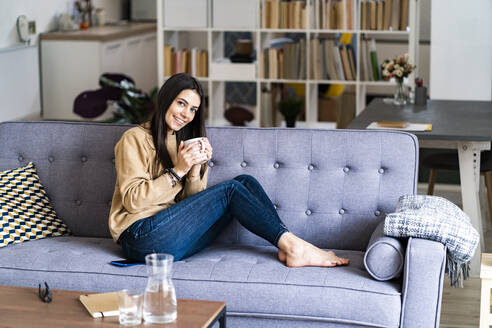 Smiling woman drinking coffee while sitting on sofa at home - GIOF11187