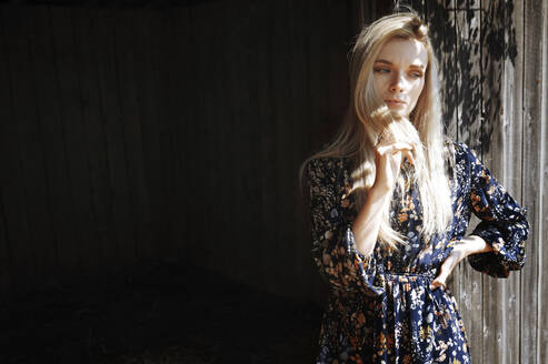 Blond woman with hand in hair day dreaming against wooden wall - AZF00186
