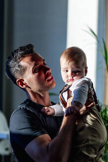 Father carrying baby boy while standing at home - PGF00433