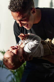 Playful father carrying baby boy while playing at home - PGF00436