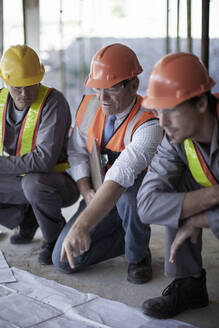 Male architect explaining plans to construction workers on site - AJOF01028