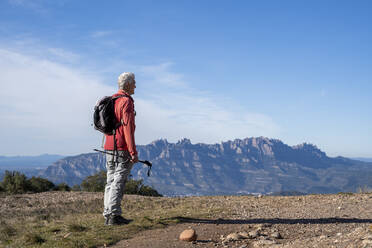 Senior man with backpack and hiking pole looking at view of Montserrat while standing on mountain at Sant Llorenc del Munt i l'Obac, Catalonia, Spain - AFVF08154