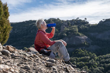 Male hiker drinking water while sitting on mountain at Sant Llorenc del Munt i l'Obac, Catalonia, Spain - AFVF08157