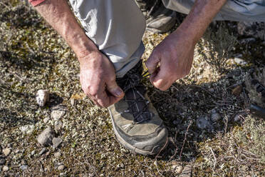 Man tying shoelace while hiking on mountain at Sant Llorenc del Munt i l'Obac at Catalonia, Spain - AFVF08160