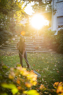 Woman sweeping with broom in garden on sunny day - AKLF00051