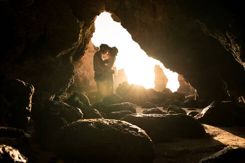 Full body side view of man and woman hugging smiling at each other while standing in entrance of cave near sea in Algar seco caves in Algarve, Portugal - ADSF20885