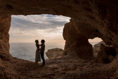Full body side view of man and woman hugging smiling at each other while standing in entrance of cave near sea in Algar seco caves in Algarve, Portugal - ADSF20888