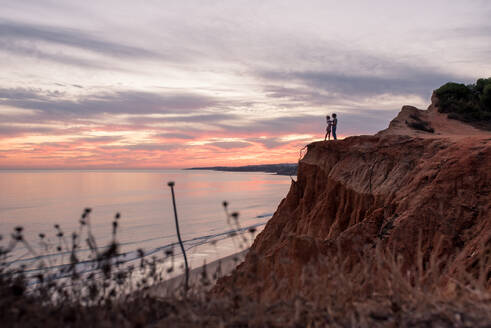Side view of unrecognizable coupe standing together in mountain cliff in the coastline during beautiful sunset in Tavira in Algarve, Portugal - ADSF20894