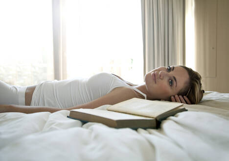 Thoughtful woman relaxing by book on bed at home - AJOF01050