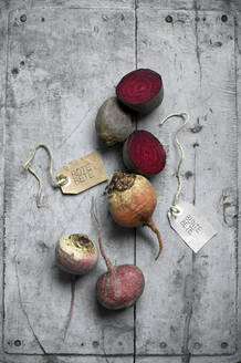 Beets and labels lying on gray wooden surface - ASF06723