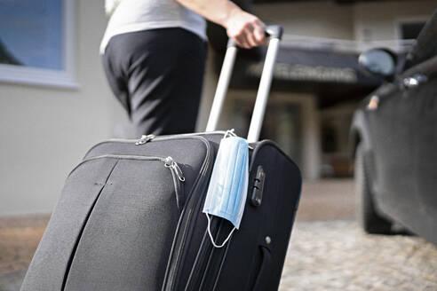 Tourist pulling wheeled luggage while walking towards hotel during coronavirus - AKLF00064
