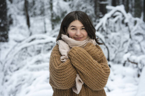 Young woman wearing sweater smiling while standing with arms crossed in forest - VPIF03577