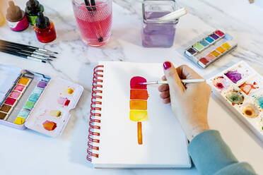 Woman painting popsickle ice cream with watercolor in book on table - GEMF04682