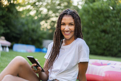 Smiling braided woman holding mobile phone while sitting in garden - AKLF00072