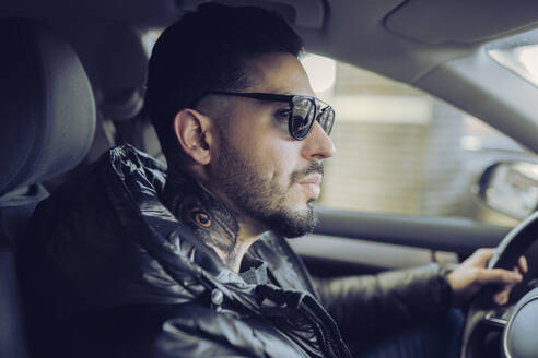Hipster man driving car while looking away - JCCMF01239